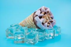 Arachidowy smaku lody rożek na górze kostek lodu na błękicie Zdjęcia Stock