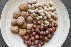 Arachidy, Hazelnuts i orzechy włoscy z Nutshells mieszanką w Naturalnym bambusa talerzu na czerń kamienia tła powierzchni, obraz royalty free
