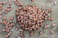 Arachis hypogaea, Raw fresh peanuts in a clay bowl on gunny background. N Royalty Free Stock Image