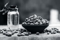 [Arachis hypogaea] Raw Groundnut in a clay bowl with groundnut oil on a gunny background. [Arachis hypogaea] Raw Groundnut in a clay bowl with groundnut oil on Stock Image