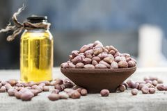 [Arachis hypogaea] Raw Groundnut in a clay bowl with groundnut oil on a gunny background. [Arachis hypogaea] Raw Groundnut in a clay bowl with groundnut oil on Stock Images