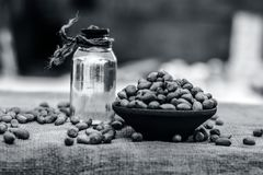 [Arachis hypogaea] Raw Groundnut in a clay bowl with groundnut oil on a gunny background. Stock Photo