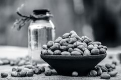 [Arachis hypogaea] Raw Groundnut in a clay bowl with groundnut oil on a gunny background. [Arachis hypogaea] Raw Groundnut in a clay bowl with groundnut oil on Royalty Free Stock Photo