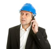 Arachitect talking on cellphone. Portrait of architect wearing blue hard hat and talking on mobile phone. Isolated on white Stock Photo