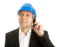 Arachitect talking on cellphone. Portrait of architect wearing blue hard hat and talking on mobile phone. Isolated on white Stock Photography