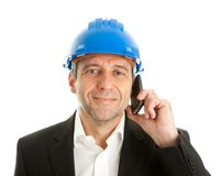 Arachitect talking on cellphone. Portrait of architect wearing blue hard hat and talking on mobile phone. Isolated on white Royalty Free Stock Image