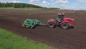 Arado do trator da máquina da agricultura e adubo espalhado no solo cultivado do campo no verão Colheitas de plantação filme