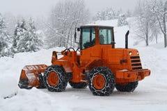 Arados de nieve anaranjados a trabajar borrando la nieve Foto de archivo