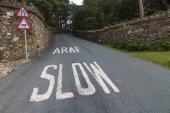 Araf, αργή, δίγλωσση άσπρη προειδοποίηση στον ουαλλέζικο δρόμο Στοκ Φωτογραφία