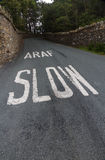 Araf, Slow, bilingual white warning on Welsh road. Welsh lane with white written Araf, Slow bilingual in Welsh and English. Wales, United Kingdom Stock Image