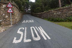 Araf, Slow, bilingual white warning on Welsh road. Stock Photography