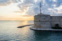 The aragonan castle on the sea during a cloudy sunset Royalty Free Stock Image