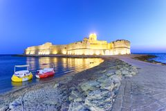 Aragonese Fortress in Calbria on a beautiful summer night with c. Olourful paddle boats, Italy Stock Images