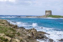 Aragonese tower on Stintino turquoise water and rocks, Sardinia,. A view of the the Torre della Pelosa tower and the Isola Piana island in the background in Stock Photography