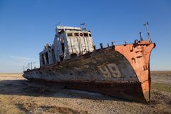 Aral sea disaster. Abandoned rusty fishing boat at the desert on the place of former Aral sea.  Stock Images