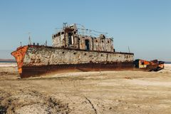 Aral sea disaster. Abandoned rusty fishing boat at the desert on the place of former Aral sea.  Stock Image