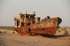 Aral sea rusty ship. Rusty ship lying in the sand at the former Soviet Aral Sea port of Moynaq in Uzbekistan royalty free stock images