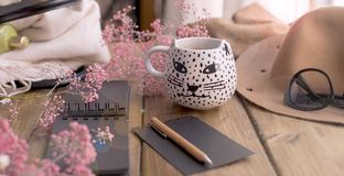 Aramatic coffee in a mug with a cat. Planning the day in notepad. Decor of pink flowers and a hat with glasses. A cozy house. Free stock images