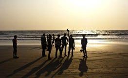 一个小组朋友现出轮廓在Arambol海滩,北部果阿 免版税库存图片