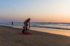 ARAMBOL BEACH, GOA, INDIA - FEBRUARY 23, 2017: Young couple are. Doing yoga on Arambol beach at sunset in Goa, India on February 23, 2017 Stock Photos
