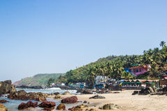 Arambol beach with stones, palms and houses, Goa, India.  Royalty Free Stock Photo