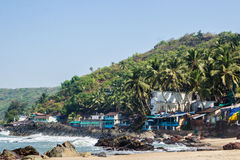 Arambol beach with stones, palms and houses, Goa, India Stock Images