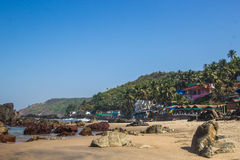 Arambol beach with stones, palms and houses, Goa, India Stock Photos