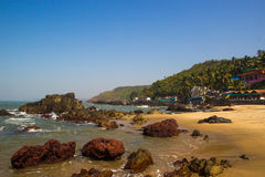 Arambol beach with stones, palms and houses, Goa, India.  Stock Photo