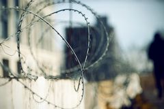 Arame farpado afiado na parte superior da cerca e da figura escura do prisioneiro fotografia de stock