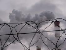 Arame farpado com fundo industrial das tubulações de fumo imagens de stock