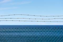 Arame farpado com opinião do mar imagem de stock
