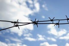 Arame farpado cruzado contra o céu Fotografia de Stock Royalty Free