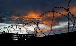 Arame farpado em um fundo das nuvens e do por do sol carmesim Fotografia de Stock Royalty Free
