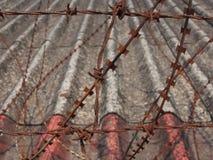 Arame farpado oxidado na cerca com fundo do telhado Foto de Stock