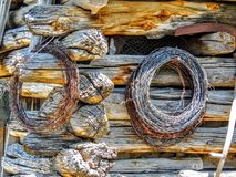 Arame farpado Rolls que pendura no close up da parede da cabana rústica de madeira Fotos de Stock Royalty Free