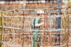 Arame farpado, uma cerca na prisão e a silhueta de uma guarda de prisão no fundo imagens de stock