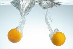 Arance che spruzzano in acqua Fotografie Stock