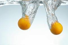 Arance che spruzzano in acqua Immagini Stock