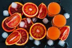 Arance e succo d'arancia rossi siciliani affettati in piccoli vetri su fondo di pietra nero Vista superiore Immagini Stock Libere da Diritti