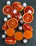 Arance e succo d'arancia rossi siciliani affettati in piccoli vetri su fondo di pietra nero Vista superiore Fotografie Stock
