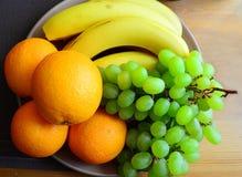 Arance ed uva verde sul piatto Immagine Stock