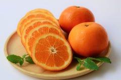 Arance, fette di arance su un piatto di legno su fondo bianco fotografie stock