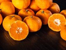 Arance fresche di metà ed intere arance con lo spazio della copia sul nero Fotografia Stock