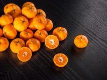 Arance fresche di metà ed intere arance con lo spazio della copia sul nero Fotografia Stock Libera da Diritti