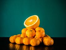 Arance fresche di metà sopra plie fresco delle arance sul wo nero Fotografia Stock Libera da Diritti