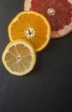arance, pompelmo, limone su un fondo nero Fotografie Stock