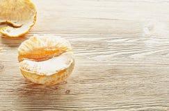 Arance sbucciate che si trovano su una tavola di legno Immagine Stock