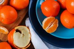 Arance sul piatto blu sulla tavola di legno scura Immagine Stock
