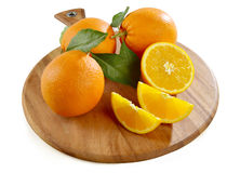 Arance sul tagliere di legno. Oranges and cloves of oranges on the wooden cutting board Stock Image