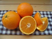 Arance tagliate su un tovagliolo della cucina Fotografia Stock